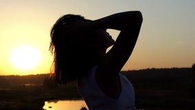 En ung brunettkvinna snygger upp med hennes händer på solnedgången i Slo-Mo arkivfilmer