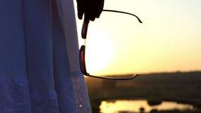 En ung brunettkvinna står med hennes solglasögon och ser solnedgång i Slo-Mo stock video