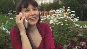 En ung brunettkvinna stannar till en vit telefon på tusenskönorna i parkera stock video