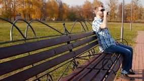 En ung caucasian man i svarta exponeringsglas sitter i parkerar på en bänk och drinkar kaffe, långsam-mo som är stilfull, kopieri stock video