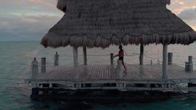 En ung caucasian man som går av dykning av en skeppsdocka in i havet nära en tropisk strandsemesterort stock video