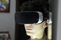 En ung Caucasian pojke bär tittaren för VR 360 i hans rum arkivfoto