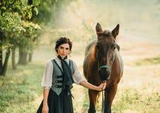 En ung dam i en tappningklänning strosar till och med skogen med hennes häst Flickan har en vit blus, en jabot, ett band arkivfoton