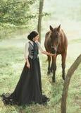 En ung dam i en tappningklänning strosar till och med skogen med hennes häst Flickan har en vit blus, en jabot, ett band royaltyfri fotografi