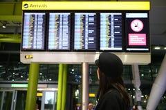 En ung dam som kontrollerar ankomsttiderna i en flygplatsterminal Arkivbilder