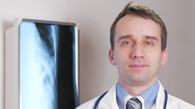 En ung doktor ser kameran och ler Mot den hängande röntgenstrålen för bakgrund av patienten Skjorta med ett band och lager videofilmer