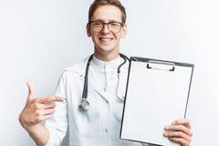 En ung doktor visar en mapp med ett tomt ark på kameran, på en vit bakgrund, för annonsering och att sätta in av text arkivfoto