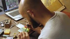 En ung elektroniktekniker med ett skägg och en skallig man löder ett elektriskt bräde som framme sitter av en bärbar dator på tab stock video