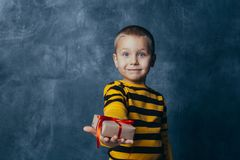 En ung emotionell pojke rymmer i hans h?nder en g?va med ett r?tt pilb?geanseende p? en bl? studiobakgrund arkivfoton