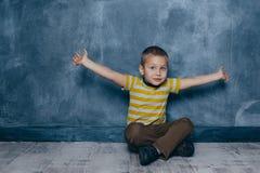 En ung emotionell pojke sitter på ett trägolv mot bakgrunden av en blå vägg i studion mänskliga sinnesrörelser arkivbild