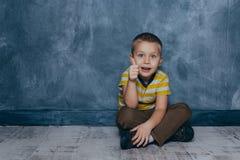 En ung emotionell pojke sitter p? ett tr?golv mot bakgrunden av en bl? v?gg i studion m?nskliga sinnesr?relser royaltyfri bild