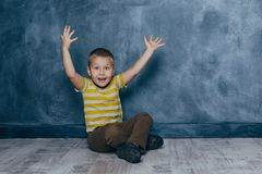 En ung emotionell pojke sitter p? ett tr?golv mot bakgrunden av en bl? v?gg i studion m?nskliga sinnesr?relser royaltyfria bilder