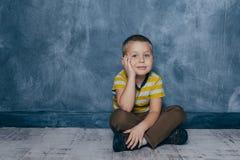 En ung emotionell pojke sitter p? ett tr?golv mot bakgrunden av en bl? v?gg i studion m?nskliga sinnesr?relser arkivbild
