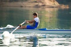 En ung enkel scullroddkonkurrent paddlar på den stillsamma sjön Arkivbilder