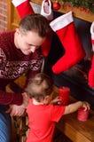 En ung fader med en behandla som ett barndotter som söker efter en gåva från jultomten i sockor Arkivfoto
