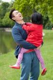 En ung fader rymmer på händer av hans dotter royaltyfri fotografi