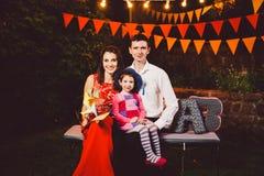 En ung familj av tre personer som sitter på en bänk i borggården nära huset, dekorerade med ljusa gula ljusa kulor som var garlan Arkivfoto