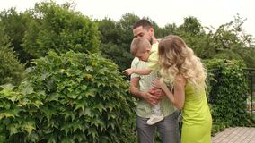 En ung familj går i en parkera bland gröna buskar stock video
