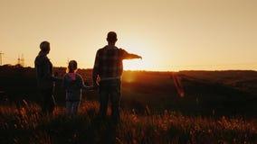 En ung familj - mamman, farsan och dottern ser tillsammans solnedgången Lyckligt tillsammans, konturer på solnedgången tillbaka s stock video