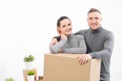 En ung familj, en man och en kvinna i gråa tröjor flyttar till nya lägenheter Askar med last på ett vitt arkivfoton