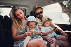 En ung familj med två litet barnbarn i taxi på sommarferie arkivfoton