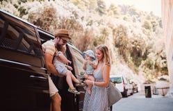En ung familj med tv? litet barnbarn som f?r ut ur taxien p? sommarferie fotografering för bildbyråer
