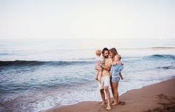 En ung familj med tv? litet barnbarn som st?r p? stranden p? sommarferie royaltyfri fotografi