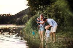 En ung familj med tv? litet barnbarn utomhus vid floden i sommar royaltyfri bild