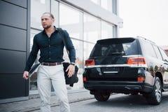 En ung fast affärsman och hans bil nära kontoret royaltyfria bilder
