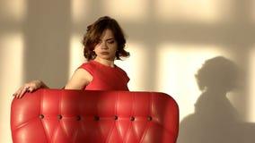 En ung flicka är ledsen och deprimerande Kvinnan trycker på den röda fåtöljen stock video
