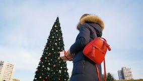 En ung flicka öppnar gåvan för ` s för det nya året nära en härlig julgran långsam rörelse lager videofilmer