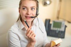 En ung flicka arbetar i en appellmitt För en arbetsplats inspelningdata På hörluren med en mikrofon telekommunikation royaltyfri fotografi