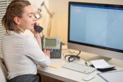 En ung flicka arbetar i en appellmitt För en arbetsplats med en telefon En mikrofon med en mikrofon serviceservice f?r illustrati royaltyfri foto