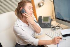 En ung flicka arbetar i en appellmitt För en arbetsplats med en telefon En mikrofon med en mikrofon serviceservice f?r illustrati arkivfoto