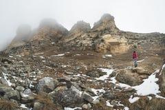 En ung flicka bara i de caucasian bergblickarna på vaggar på foten som ligger av snön Rocks packar dimmigt in Royaltyfri Bild