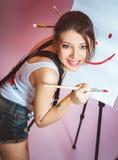 En ung flicka befl?ckas med m?larf?rg fotografering för bildbyråer