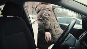 En ung flicka, chauffören, kommer ut ur kabinen av hans bil lager videofilmer