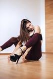 En ung flicka dansar på höga häl som utför dansflyttningar, medan sitta på golvet fotografering för bildbyråer