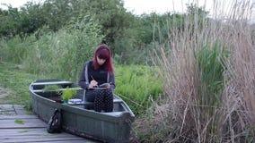 En ung flicka drar ett fartyg i den öppna luften stock video