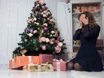 En ung flicka framme av ett sammanträde framme av en julgran, ögon stängde sig med hennes händer i förväntan av att välja en gåva arkivfoto