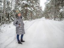 En ung flicka g?r i vinterskogen och tycker om tystnad royaltyfria foton