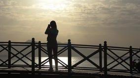 En ung flicka gör ett foto på en smartphone som står på bron på soluppgång lager videofilmer