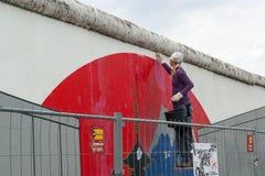 En ung flicka gör ren Berlin Wall, East Side Gallery, Berlin arkivbilder