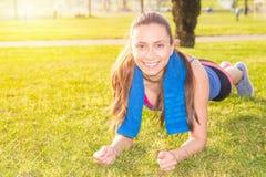 En ung flicka gör sportövningar i en parkera på gräset Arkivbild