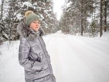En ung flicka g?r i vinterskogen och tycker om tystnad arkivbilder