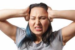 En ung flicka griper hennes huvud med båda händer och visar ett strängt huvud smärtar P? vitbakgrund arkivfoto
