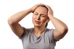 En ung flicka griper hennes huvud med båda händer och visar ett strängt huvud smärtar P? vitbakgrund royaltyfri fotografi