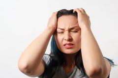En ung flicka griper hennes huvud med båda händer och visar ett strängt huvud smärtar P? vitbakgrund fotografering för bildbyråer