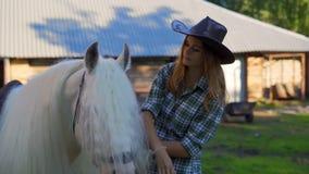 En ung flicka i en cowboyhatt tar omsorg av och smeker en häst på en djur lantgård på en varm sommardag långsam rörelse stock video