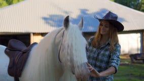 En ung flicka i en cowboyhatt tar omsorg av och smeker en häst på en djur lantgård på en varm sommardag långsam rörelse arkivfilmer